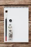 Leerer Sketchbook mit schwarzem Farben- und Bürstenmodell Lizenzfreies Stockbild