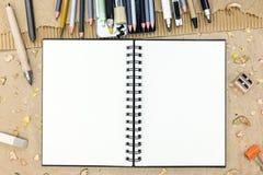 Leerer Sketchbook und Bleistifte für das Zeichnen auf braunes künstlerisches backg Lizenzfreies Stockbild