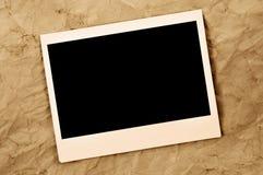 Leerer sofortiger Fotorahmen auf einem alten Papier Stockbilder