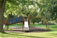 Leerer Spielplatz mit Schwingen und Dia auf Rasenfläche stockbild