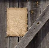 Leerer Steckbrief auf verwitterter Plankenholztür Stockbild