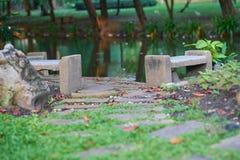 Leerer Stein oder Zement setzt auf Unschärfewasserteich in Garten backg auf die Bank stockbild