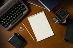 Leerer steno Notizblock auf einem Schreibtisch unter Weinlesejournalismusstützen stockbild