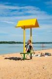 Leerer Strand mit einer Bank mit einer Überdachung auf der Küste Stockfoto