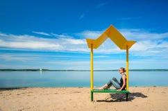Leerer Strand mit einer Bank mit einer Überdachung auf der Küste Stockbild