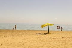 Leerer Strand mit Regenschirm Stockfotos