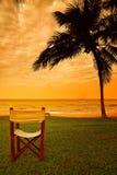 Leerer Strandstuhl an der Küste während des Sonnenuntergangs Lizenzfreie Stockfotos