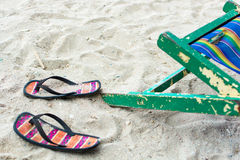 Leerer Strandstuhl und Flipflops Stockfoto