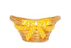 Leerer Strohkorb mit einem gelben Farbband und einem Bogen Lizenzfreie Stockfotos