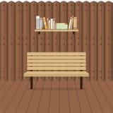Leerer Stuhl auf hölzerner Wand mit Bücherregal Lizenzfreie Stockfotografie