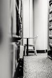 Leerer Stuhl und Schreibtisch in einem ruhigen Bibliotheks-Winkel Stockfotografie