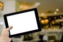 Leerer Tablet-PC in der Hand im Caféstangeninnenraum Lizenzfreie Stockfotos