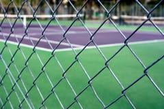 Leerer Tennisplatz hinter Drahtzaun Stockfotografie