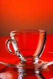 Leerer transparenter Glasbecher auf rotem Hintergrund Stockfotografie