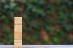 Leerer vier StaplungsHolzklotz auf hölzerner Tabelle mit grünem Naturhintergrund und Raum am rechten Gebrauch für Input Ihr Text lizenzfreies stockbild