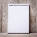 Leerer weißer Bilderrahmen auf der Wand und dem Boden Stockbilder