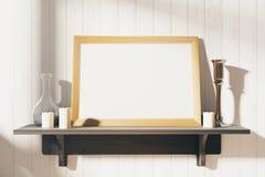 Leerer weißer Bilderrahmen mit Kerzenständern auf braunem hölzernem shel Stockbild