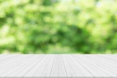 Leerer weißer Holztisch mit Naturgrün verwischte Hintergrund Stockfotografie