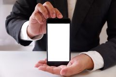 Leerer weißer Schirm Geschäftsmannholding Smartphone vorwärts für Ihren Text oder Bild stockfotografie