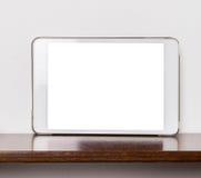 Leerer weißer Tablettenschirm auf hölzernem Regal Stockfoto