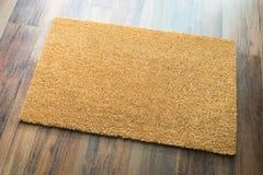 Leerer willkommener Mat On Wood Floor Background bereit zu Ihrem eigenen Text stockfotos