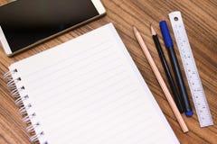 Leeres Anmerkungsbuch mit Bleistiftstift und Smartphone auf hölzerner Tabelle legen herein Lizenzfreie Stockbilder