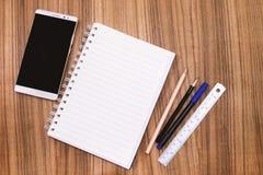 Leeres Anmerkungsbuch mit Bleistiftstift und Smartphone auf hölzerner Tabelle legen herein Stockbilder