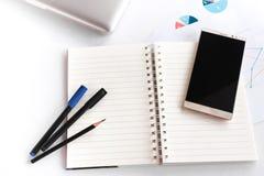 Leeres Anmerkungsbuch mit dem Bleistiftstift Laptop- und Smartphonekonzept Lizenzfreie Stockfotos