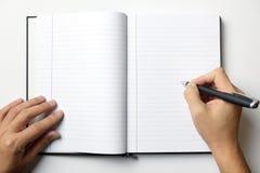 Leeres Anmerkungsbuch mit den Mannhänden halten einen Stift stockfoto