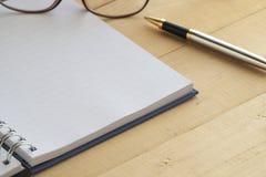 Leeres Anmerkungsbuch mit silbernem Stift und Gläsern Stockfoto