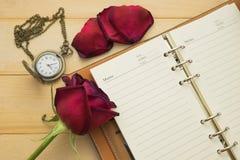 Leeres Anmerkungsbuch, Taschenuhr und rote Rosen setzten an hölzernes lizenzfreie stockfotos