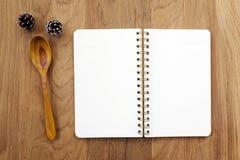 Leeres Anmerkungsbuch und hölzerner Löffel auf Tabelle Lizenzfreies Stockbild