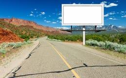 Leeres Anschlagtafel-Zeichen durch Landstraße in der Wüste Lizenzfreie Stockfotografie