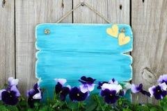 Leeres antikes blaues Zeichen mit purpurroten Blumen (Pansies) Stockbild