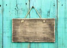 Leeres antikes hölzernes Zeichen, das an beunruhigter Holztür des blauen Grüns hängt Lizenzfreie Stockfotos