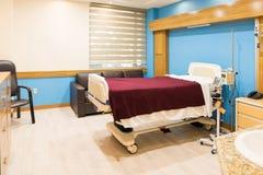 Leeres Bett in einem ausgerüsteten Krankenhauszimmer stockfotografie