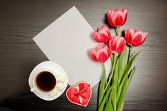 Leeres Blatt des Papiers, der rosa Tulpen und des Bechers Kaffees Schwarze Tabelle Beschneidungspfad eingeschlossen Stockbild