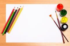 Leeres Blatt mit Farbe und Bleistiften auf Schreibtisch, Kunstkonzept Lizenzfreie Stockbilder