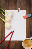 Leeres Blatt Papier, Bleistifte, Radiergummi, Blumen und Tasse Kaffee auf dunklem hölzernem Schreibtisch Stockbild