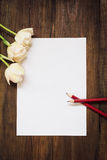 Leeres Blatt Papier, Bleistifte und Blumen auf dunklem hölzernem Schreibtisch Stockbild