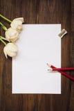 Leeres Blatt Papier, Bleistifte und Blumen auf dunklem hölzernem Schreibtisch Stockbilder
