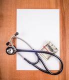 Leeres Blatt Papier des Stethoskops und Geld Stockfotos