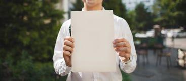 Leeres Blatt Papier Schablone für Text in den Händen eines Mannes Stockfotografie