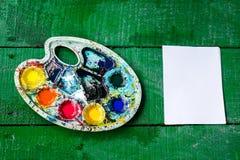 Leeres Blatt und bunte Palette auf einem grünen Holztisch Beschneidungspfad eingeschlossen Stockbild