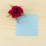 Leeres blaues Papier und rosafarbene Blume auf hölzernem Hintergrund Stockfoto