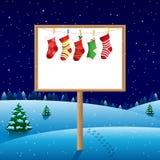 Leeres Brett auf Winternacht mit Weihnachtssocken stockfotografie