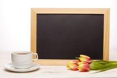 Leeres Brett, Blumen und Tasse Kaffee Stockfoto