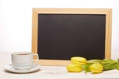 Leeres Brett, Blumen und Tasse Kaffee Lizenzfreies Stockfoto