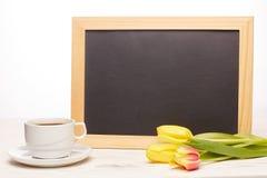 Leeres Brett, Blumen und Tasse Kaffee Lizenzfreie Stockbilder