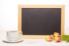 Leeres Brett, Blumen und Tasse Kaffee Stockbilder